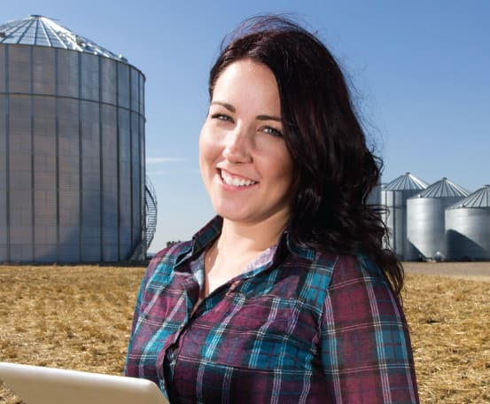 A lady holding a tablet with silos in the background.